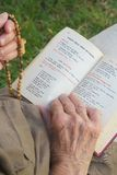 An open franciscan prayer book in Italian language and anglican prayer beads with cross Stock Photos