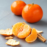 Open fresh mandarin with cinnamon sticks on gray background Stock Photo