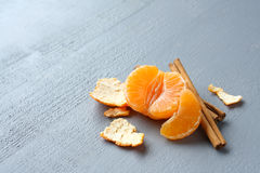 Open fresh mandarin with cinnamon sticks on gray background Royalty Free Stock Photos