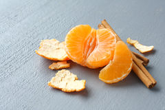 Open fresh mandarin with cinnamon sticks on gray background Stock Image