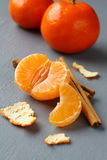 Open fresh mandarin with cinnamon sticks on gray background Stock Photo
