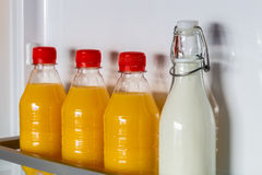 Open fridge filled with orange juice and milk Stock Images