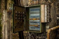 Open fuse box in industry ruins. Open metal fuse or control electricity box in abandoned industry ruins royalty free stock images