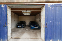 Open garage door with two cars inside. Bristol, United Kingdom - Mar 7, 2017: Open garage door with two luxury car inside - security and safety of the Royalty Free Stock Images