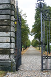 The open gate. An open iron gate with a road that fade in the distance Royalty Free Stock Images