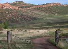 Open Gate. An open gate beckons for you to follow the dirt road to the foot hills and mountains beyond Royalty Free Stock Photos