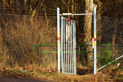 Open gate. An open aluminum gate with netted fence on both sides. Gate is somewhat bent which suggests forced entry. Fence is damaged Stock Image