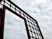Open gate and cloudscape. Low angle view of open red metal gate with white cloudscape background Stock Photography