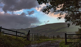 Open Gate. With the Glyn mountain beyond. Rain poursdown on the right and left of the image as clear skies break over the mountain. Pant-y-Brad, Rhondda, Wales Stock Images