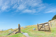 Open gate on hillside. Open old wooden farm gate on hillside under blue sky with light wispy clouds royalty free stock photography