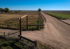 Open gate at junction of dirt roads Stock Photography