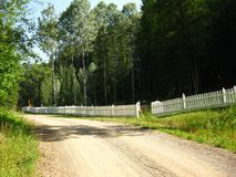 Open gate at long white fence Stock Photo