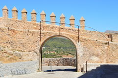Open gate of a medieval castle wall. Located in a mediterranean village. Photo taken from the inside of the castle. Wall has towers as decoration. Through the Royalty Free Stock Images