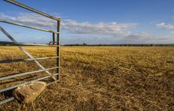 Open gate to field. Steel gate entrance to harvested field countryside Royalty Free Stock Image