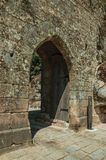 Open gateway with wooden door on a stone wall royalty free stock photography
