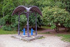 Open gazebo with blue water columns in the park Royalty Free Stock Photos