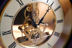 Open-gearing clock on a table. Blur, shadows and lights Stock Images