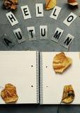 Open geel notitieboekje, bladeren, de herfst van brievenhello op grijze backg Royalty-vrije Stock Afbeelding