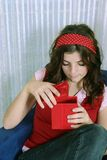 Open the gift. Curious teenager looking into  a red box to see a gift Stock Photo