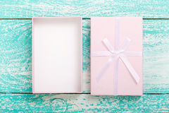 Open gift box on blue vintage wooden desk top view. Stock Photo