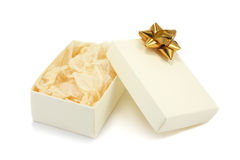 Open Gift Box with Bow. A open cream textured cardboard gift box with a gold metallic bow and crumpled tissue paper on a white background Royalty Free Stock Photo