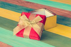 Open gift box on color wooden background Stock Photos