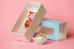 Open gift box with colorful cake balls and candies with sprinkle. Closeup photo of open gift box with colorful cake balls and candies with sprinkles over pink Stock Photos