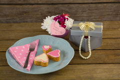 Open gift box with flower vase and heart shape cookies. On wooden plank Stock Photography
