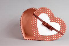 open gift box in heart shape on grey background stock photos