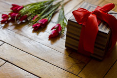 Open gift box present with red bow and strips on wooden backgroud Stock Images