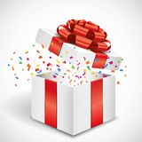 Open gift box with red bow and confetti Royalty Free Stock Photos
