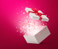 Open Gift Box with Ribbon and Hearts Confetti. Hearts confetti popping out from white gift box Stock Photo