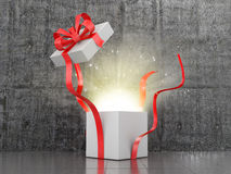 Open gift box from which comes the glow. Stock Photos