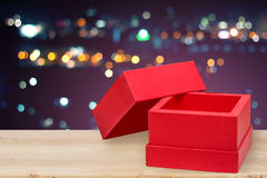Open gift box on wooden table with city lights Stock Image