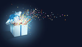Open gift with fireworks from confetti. Stock Photo
