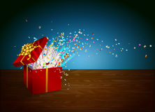 Open gift with fireworks from confetti on wooden background. . Stock Image