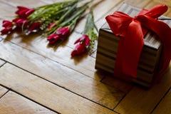 Open giftdoos huidig met rode boog en stroken op houten backgroud Stock Afbeeldingen