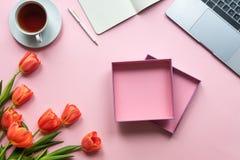 Open giftdoos op roze achtergrond met laptop, bloemen en kop thee royalty-vrije stock afbeeldingen