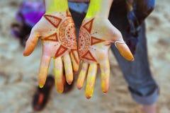 Open girls palms closeup with sun Holi fest. Open girls palms closeup with pictures of the sun made by henna on Holi fest stock photography