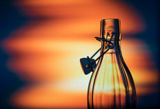 Open glass bottle in front of a creative background Royalty Free Stock Photos