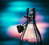 Open glass bottle in front of a creative coloured background Royalty Free Stock Image
