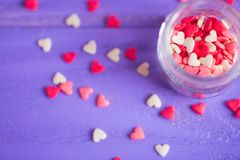 Open glass jar filled with many little candies in form of hearts. On purple wooden background. St. Valentine Day card Stock Image