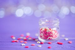 Open glass jar filled with many little candies in form of hearts. On purple bokeh background. St. Valentine Day card Royalty Free Stock Images