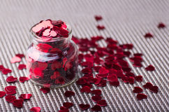 Open glass jar filled with many red little hearts Royalty Free Stock Images