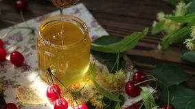 Open glass jar of liquid honey and honey dipper, bunch of linden flowers and red cherry on wooden surface. Ray of sunlight. Dark rustic style., dynamic scene stock footage