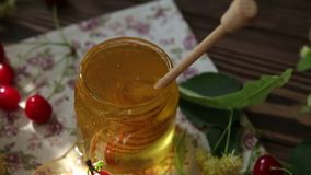 Open glass jar of liquid honey and honey dipper, bunch of linden flowers and red cherry on wooden surface. Ray of sunlight. Dark rustic style., dynamic scene stock video footage