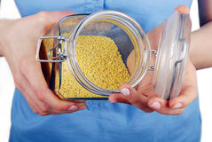 Open glass jar with millet Royalty Free Stock Images
