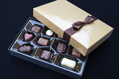 Open golden chocolate box. With a brown ribbon Stock Photo
