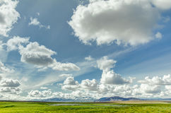Open grassland with cloudscape and mountains in background. Iceland. Open grassland with clouds and snow covered mountains. Beautiful landscape and cloudscape Stock Photos
