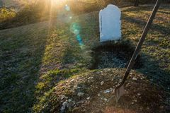 Open grave with shovel at sunset. An open grave with a shovel stuck in a pile of dirt at sunset. Death, the afterlife, Halloween all come to mind royalty free stock photo